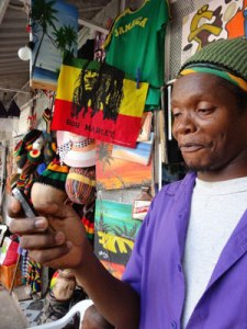 A man in Jamaica  uses his mobile phone to access financial services.